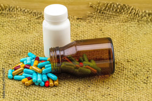 colorful pills and bottle tablets on brown sack fabric