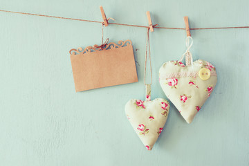 christmas image of fabric hearts and empty card for adding text hanging on rope in front of blue wooden background. retro filtered