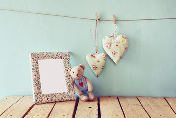 teddy bear over wood table next to blank photo frame and fabric hearts. retro filtered image