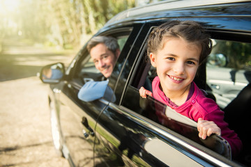 a girl is smiling, passing her head through the car window