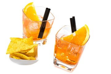 Fototapete - top of view of two glasses of spritz aperitif aperol cocktail with orange slices and ice cubes near tacos chips