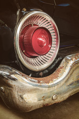 Rusted rear light and bumper of a classic car