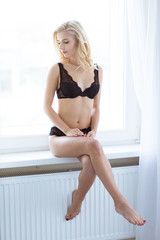 Sexy girl in lingerie sitting on the windowsill