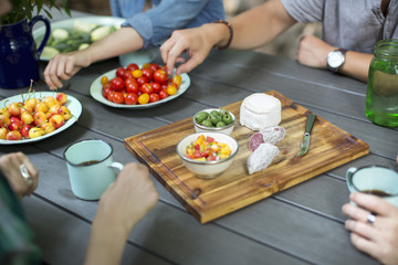 A group of people gathered around a table with plates of fresh fruits and vegetables, and a round cheese and salami on a chopping board.