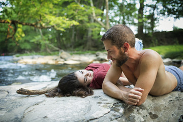 A young man and woman lying on the rocks on a river bank.