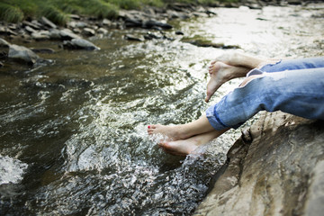 A woman in fashionable jeans with a rip, with her feet in the cool flowing waters of a river.