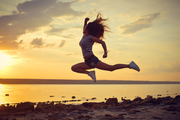 Modern style dancer posing in mid air on beach