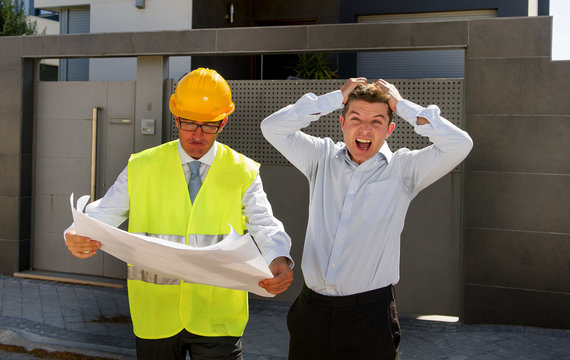unhappy customer in stress and constructor foreman worker with helmet and vest arguing outdoors on new house building blueprints