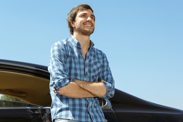 Handsome guy leaning on his car