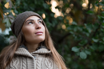 Beautiful woman in a knitted garment and cap in the park