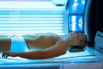 young man relaxing during solarium treatment
