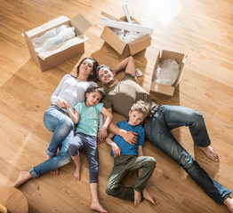 a family laying in their new flat with cardboard boxes