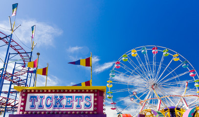 Acrylic Prints Carnaval Ticket Booth and Carnival Rides against blue sky