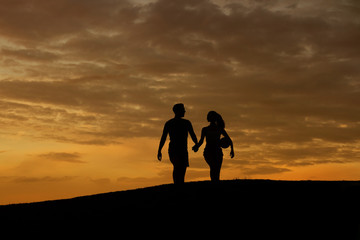 Loving couple of sportsmen walk on the evening hills.
