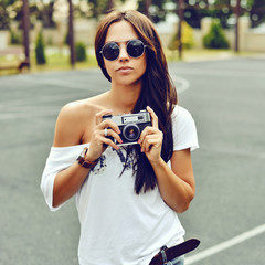 Beautiful hipster girl with old camera