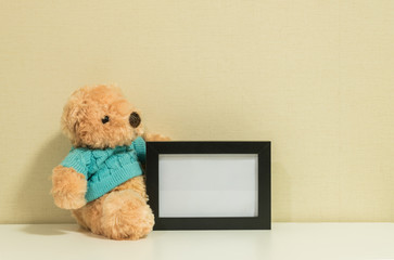 Frame for a photo with brown bear doll on wall room background