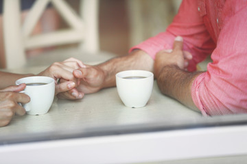 Couple drinking tea and talking in cafe close-up