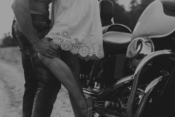 Muscled guy and beautiful girl on a motorcycle ride on a field road. Beautiful and powerful motorcycle. Free lifestyle. Photo for motorcycle magazines, posters and websites.