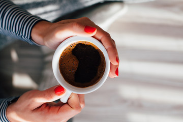 Closeup of woman holding a hot cup of coffee