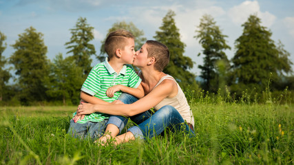 Mother and son kissing, posing for an outdoor portrait