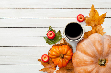 Cup of coffee and pumpkin with leafs
