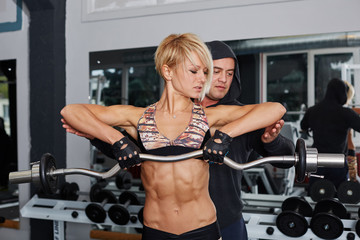 Personal trainer helping blonde woman in press of weight