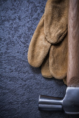 Leather safety gloves claw hammer on black background vertical v