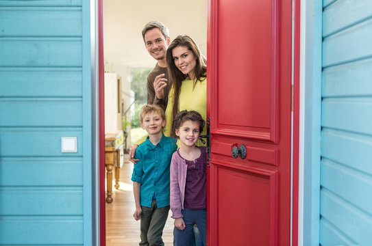 family is opening their stylish red door to welcome the guest