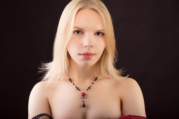 Portrait of a young beautiful lady with necklace isolated over black background