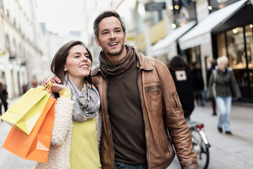 Stylish couple walking in a cobbled car-free street, shopped