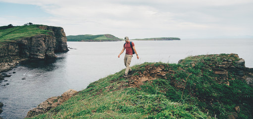 Hiker man walking on coastline near the sea