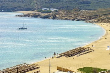 Aerial view of Elia beach on greek island Mykonos, Greece. A view of the blue sea, sunbeds, sun umbrellas, golden sand and a sailboat in the water on a summer day.