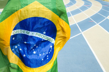 Athlete wearing Brazilian flag against a blue and tan running track background