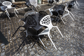 Black and white plastic chairs in a street cafe