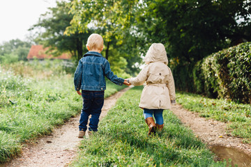 Little boy and girl walking in nature together