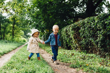 Happy little boy and girl walking in nature