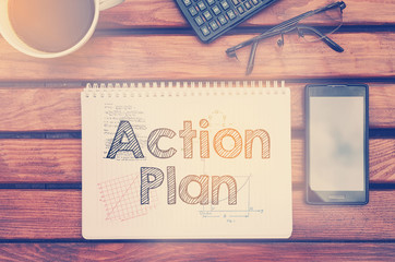 Notebook with text inside Action Plan on table with coffee, mobile phone