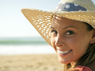 happy girl smiling portrait in the beach  wearing a picture hat with the sea and horizon in the background