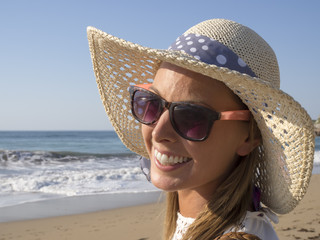 happy blonde girl smiling portrait in the beach  wearing hat and sunglasses