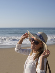 happy fashion blonde girl smiling portrait in the beach  wearing hat and sunglasses