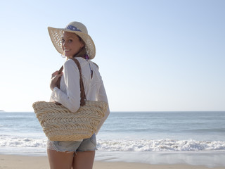 happy fashion blonde girl smiling portrait in the beach  wearing hat, bat  and shorts jeans