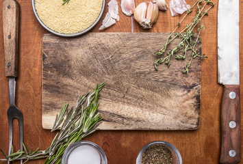 Couscous herb knife meat fork garlic and salt seasoning cutting board. Ingredients on wooden rustic background close up top view