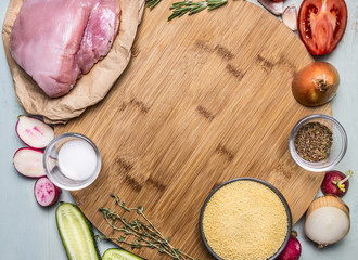 Ingredients for cooking a turkey breast couscous cucumber radish tomato onion seasoning herbs. on wooden rustic background close up top view space for text