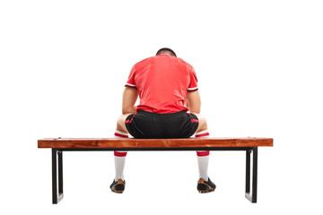 Sad football player sitting on a wooden bench