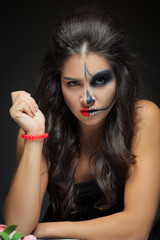 beautiful woman with make-up skeleton. half-face