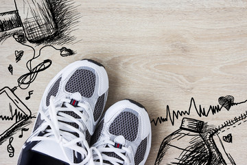 Sport shoes and hand drawn design on the wooden floor. Healthy c
