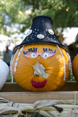 decorated pumpkin as an old lady with hat and makeup.  good for seasonal