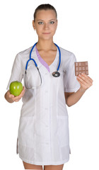 Woman doctor holding an apple and chocolate symbolize proper nutrition, diet.