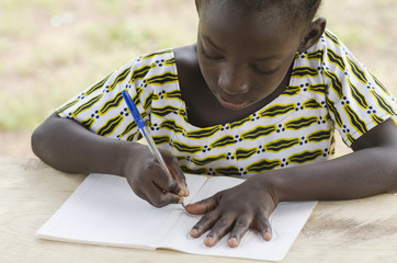 Black African Girl drawing and writing in her workbook in an African school in Bamako, Mali. Educational symbol for Africa.