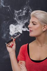 Junge attraktive blonde Frau raucht eine e-zigarette